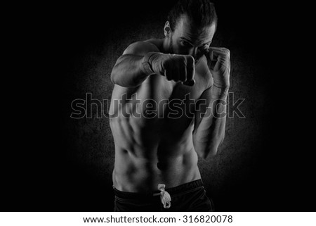 Muscular young man in boxing gloves and shorts  - stock photo