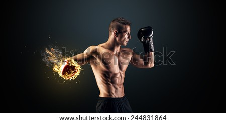 Muscular young man in boxing gloves and shorts shows the different movements and strikes in the studio on a dark background - stock photo
