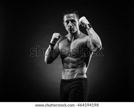 Muscular young man in boxing gloves and shorts shows the different movements and strikes in the studio on a dark background