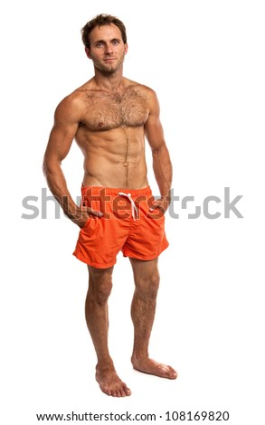 Muscular young man in swimwear standing on white background