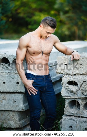 Muscular young man near concrete slab. - stock photo
