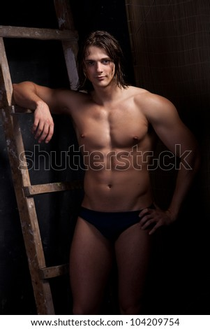 Muscular young man on black background near the staircase - stock photo