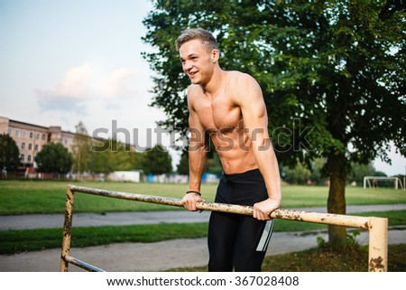 Muscular young man pull ups the horizontal bar. Street workout. - stock photo