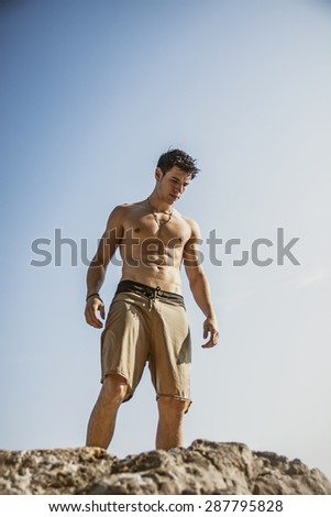 Muscular young man shirtless standing on rock against the sky, seen from below perspective - stock photo
