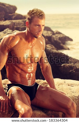 Muscular young man sitting on rocks at the beach in golden light