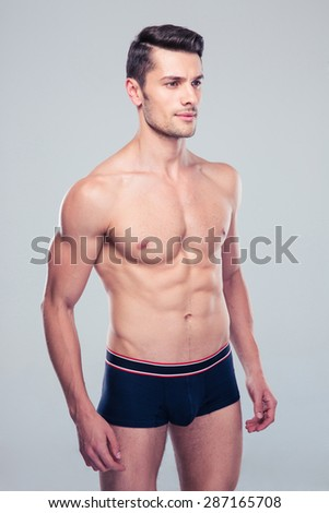 Muscular young man standing over gray background - stock photo