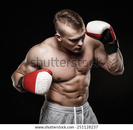 Muscular young man wearing boxing gloves
