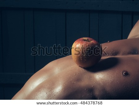 Muscular young man with apple fruit on athletic bare torso closeup, healthy food and diet