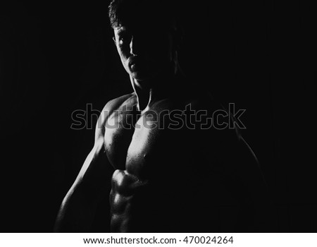 Muscular young man with athletic bare body standing, black and white