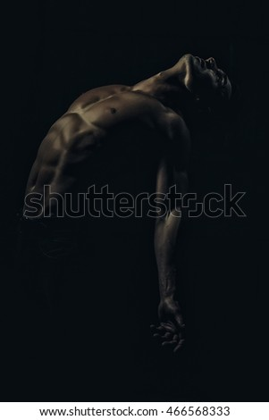 Muscular young man with athletic bare body standing on black background