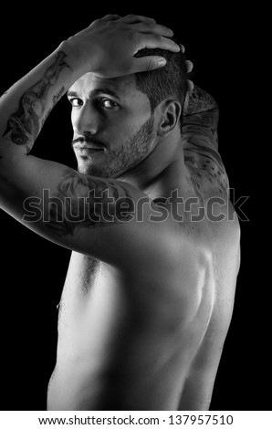 Muscular young man with many tattoos - stock photo