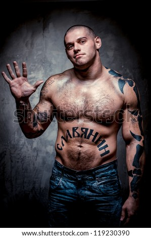 Muscular young man with many tattoos posing over grey background - stock photo
