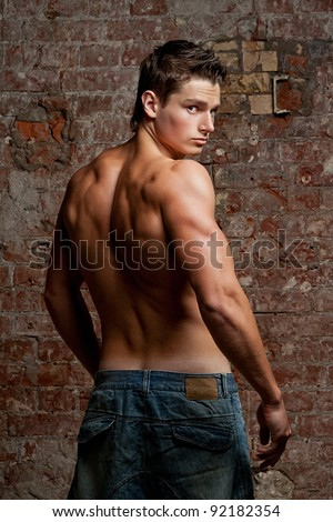 Muscular young naked sexy boy in jeans looking over your shoulder