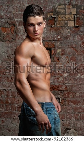 Muscular young naked sexy boy posing in blue jeans on the background of a brick wall