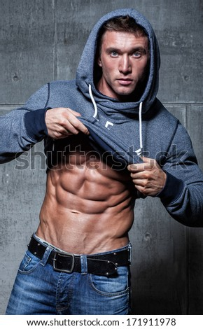 Muscular young sexy bodybuilder takes off his hooded Jersey - stock photo