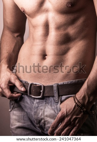 Muscular young sexy guy posing in studio in jeans and naked torso  - stock photo