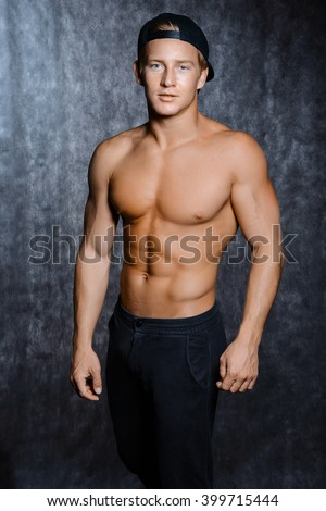 Muscular young sexy man  in a cap with a naked torso on black background - stock photo