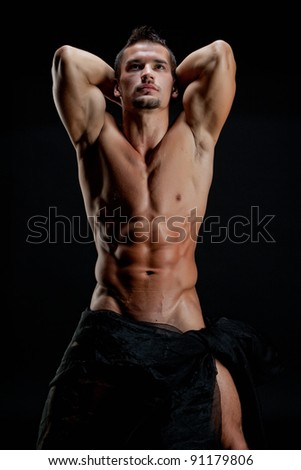 Muscular young sexy naked cute man wrapped in a silk cloth with hands behind head - stock photo