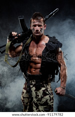 Muscular young sexy naked soldiers with knives and weapons in army clothes and flak jacket in the smoke - stock photo