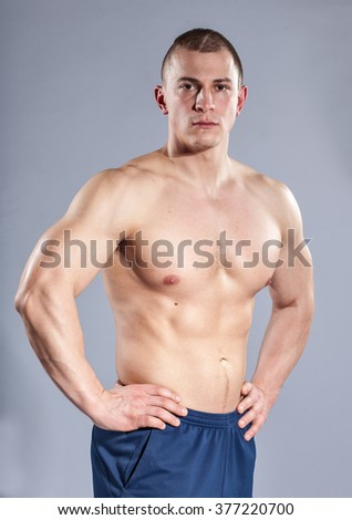 muscular young topless man on gray background - stock photo