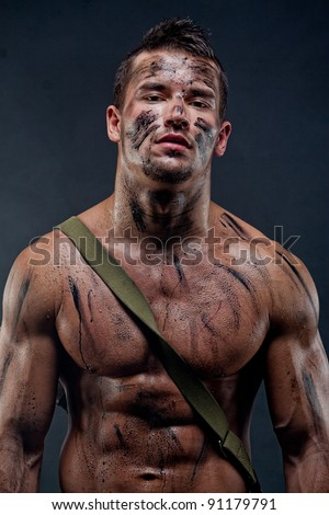 Muscular young wet sexy naked dirty soldiers with weapons behind - stock photo