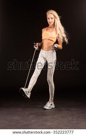 Muscular young woman athlete with a skipping rope on black background.