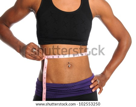 Muscular young woman measuring waist with tape isolated over white background - stock photo