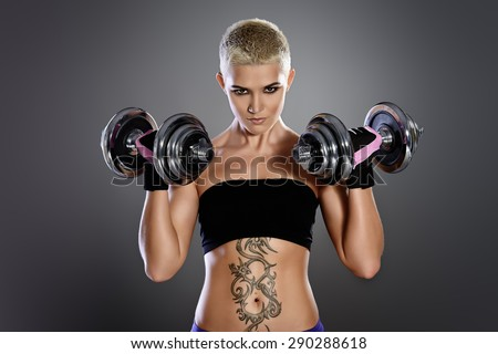 Muscular young woman with beautiful athletic body doing exercises with dumbbells. Fitness, bodybuilding. Health care. - stock photo