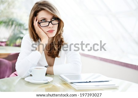 Muse on fall to thinking / photo of beautiful woman sitting in a coffee house