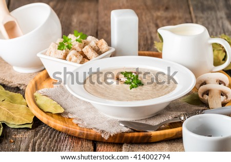 Mushroom cream soup in a white bowl on wooden table
