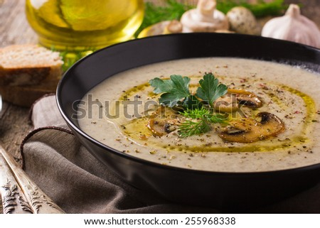 Mushroom cream soup on rustic background, top view - stock photo