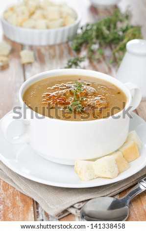 Mushroom cream soup with croutons and thyme in a bowl vertical - stock photo