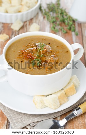 Mushroom cream soup with croutons and thyme in a bowl vertical close-up