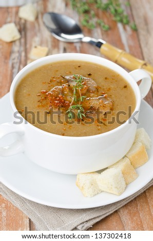 Mushroom cream soup with croutons and thyme in a bowl vertical, top view close-up - stock photo