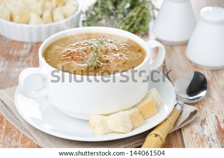 Mushroom cream soup with croutons and thyme in the white bowl - stock photo