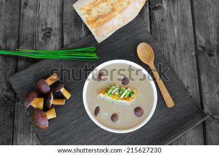 Mushroom cream soup with toast and fresh herbs on wood table - stock photo