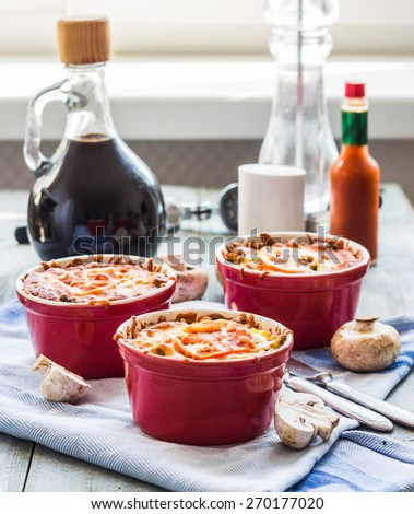 mushroom julienne with tomato and cheese in red pots, lunch on gray board - stock photo