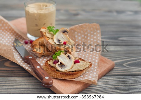 mushroom pate with cranberries and parsley on grilled crusty bread on wooden background - stock photo