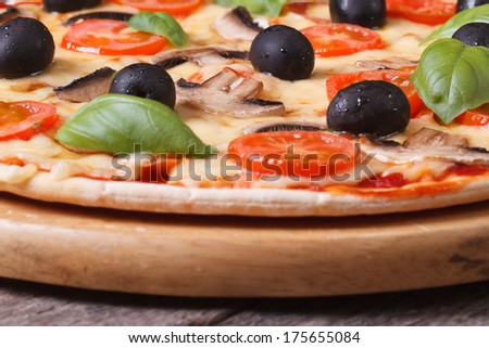 mushroom pizza with olives, tomatoes and basil on the table. horizontal   - stock photo