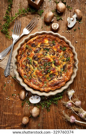 Mushroom quiche on a rustic wooden table. Delicious and nutritious vegetarian dish - stock photo