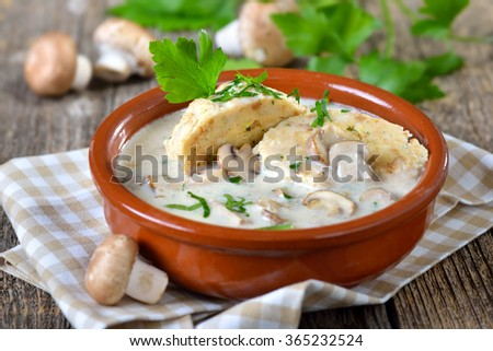 Mushroom sauce with bread dumplings served in a ceramic bowl on a wooden table - stock photo