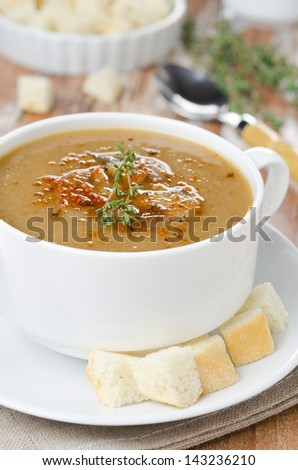 Mushroom soup in a bowl with croutons and thyme vertical - stock photo