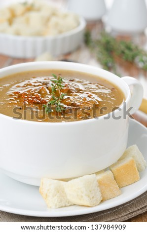 Mushroom soup in a white bowl with croutons and thyme close-up selective focus
