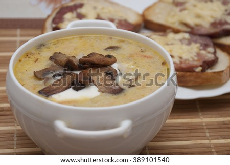Mushroom soup on a table , sandwiches with grilled meat behind - stock photo