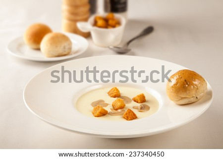Mushroom soup with bread on the table - stock photo