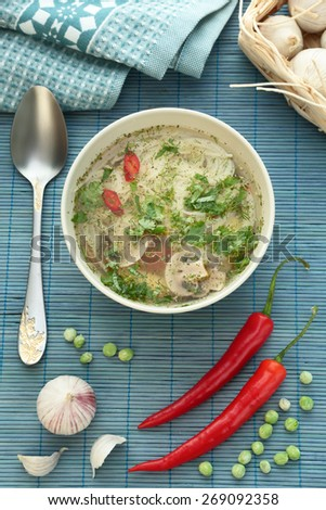 mushroom soup with noodles on a blue background with a spoon, pepper, garlic and red pepper - stock photo