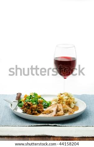 Mushroom stuffed pork loin roast, with dressing, gravy, mashed potatoes, salad and red wine - stock photo