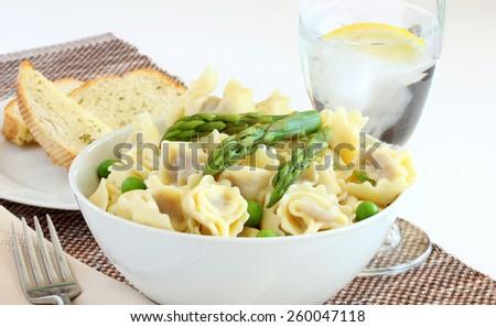 Mushroom stuffed tortellini, fresh steamed peas and spring asparagus - stock photo