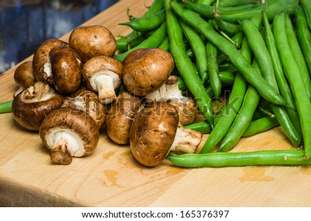 Mushrooms and green beans on a wooden cutting board in kitchen