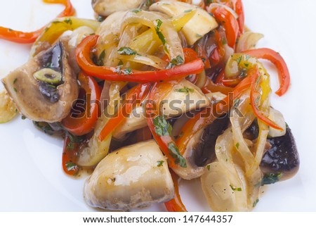 Mushrooms and vegetables garnish on white plate close-up
